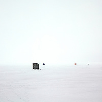 Ice fishing shack and fisherman walking through the frozen fog on Lake Mendota in Madison, Wisconsin.