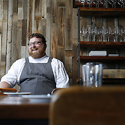 SHOT 8/15/13 4:11:17 PM - Justin Brunson, Owner and Executive Chef at Old Major restaurant in Denver, Co. Includes images of menu items : The Nose to Tail Plate : confit rib, pork chop, crispy belly, city ham, crispy ear, Denver Bacon Co. barbecue beans, cole slaw and corn bread $29 and Pan Seared Scallops : baby vegetables, fregola, spinach purée, toasted pine nuts, roasted garlic vinaigrette $27. The restaurant focuses on heritage-raised meats from Colorado farms, features an in-house butchery program and bills itself as contemporary farmhouse cuisine. (Photo by Marc Piscotty / © 2013)