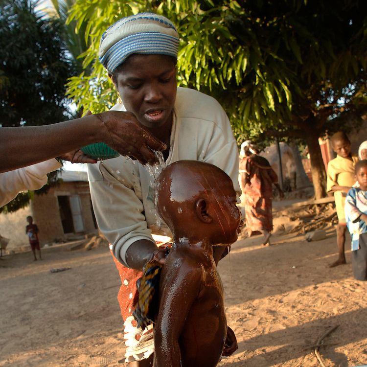 A child is comforted after a Scarification Ceremony in ...