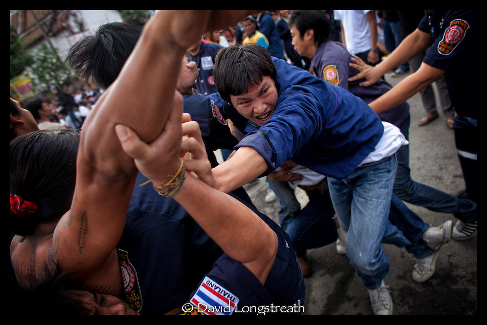 A Sak Yant devotee is restrained after working himself into a frenzy during festivities at the Wat Bang Phra tattoo festival in Nakhon Chai Si province on the outskirts of Bangkok, Thailand.
