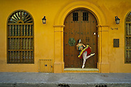 Model relased photo of Gina, a Colombian professional ballet dancer in Cartagena peaking through a wood door.