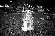 A black and white photo of an all but forgotten headstone in an ancient cemetery filled with hundreds of unnamed graves which are occupied by unknown Confederate Soldiers in Stone Mountain Georgia.