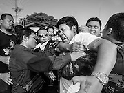 """07 MARCH 2015 - NAKHON CHAI SI, NAKHON PATHOM, THAILAND: Volunteers bring a man out of a trance state at the Wat Bang Phra tattoo festival. Wat Bang Phra is the best known """"Sak Yant"""" tattoo temple in Thailand. It's located in Nakhon Pathom province, about 40 miles from Bangkok. The tattoos are given with hollow stainless steel needles and are thought to possess magical powers of protection. The tattoos, which are given by Buddhist monks, are popular with soldiers, policeman and gangsters, people who generally live in harm's way. The tattoo must be activated to remain powerful and the annual Wai Khru Ceremony (tattoo festival) at the temple draws thousands of devotees who come to the temple to activate or renew the tattoos. People go into trance like states and then assume the personality of their tattoo, so people with tiger tattoos assume the personality of a tiger, people with monkey tattoos take on the personality of a monkey and so on. In recent years the tattoo festival has become popular with tourists who make the trip to Nakorn Pathom province to see a side of """"exotic"""" Thailand.   PHOTO BY JACK KURTZ"""