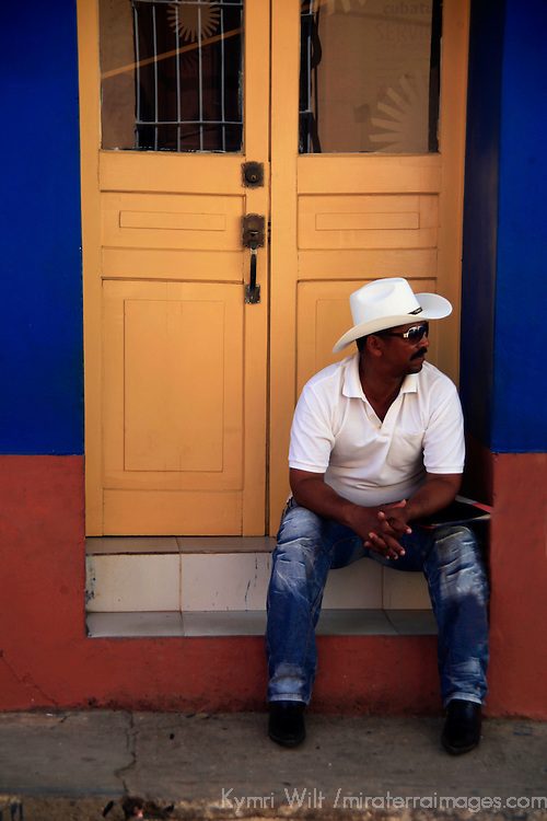 Central America, Cuba, Trinidad. Cuban man sitting on stoop in Trinidad.