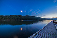 The quarter Moon in conjunction with Mars (right of Moon) and Spica (left of Moon) reflected in the waters of Reesor Lake, Alberta in Cypress Hills Interprovincial Park. Taken on July 5, 2014 as part of a 400 frame motion control time-lapse. This is with the 14mm Rokinon lens and Canon 6D, for 1.6 seconds at f/2.8 and ISO 800.