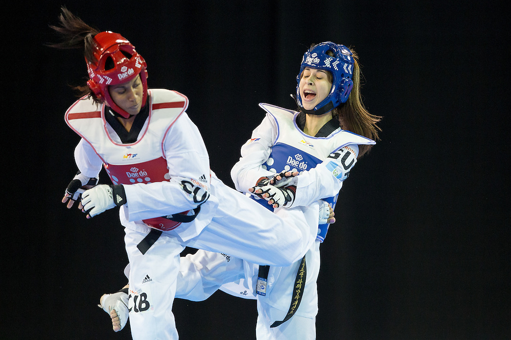 Yamicel Nunez of Cuba kicks Coralia Abadia of Guatemala during their 1/8 round contest in the -57kg weight class of Taekwondo at the 2015 Pan American Games in Toronto, Canada, July 20,  2015.  AFP PHOTO/GEOFF ROBINS