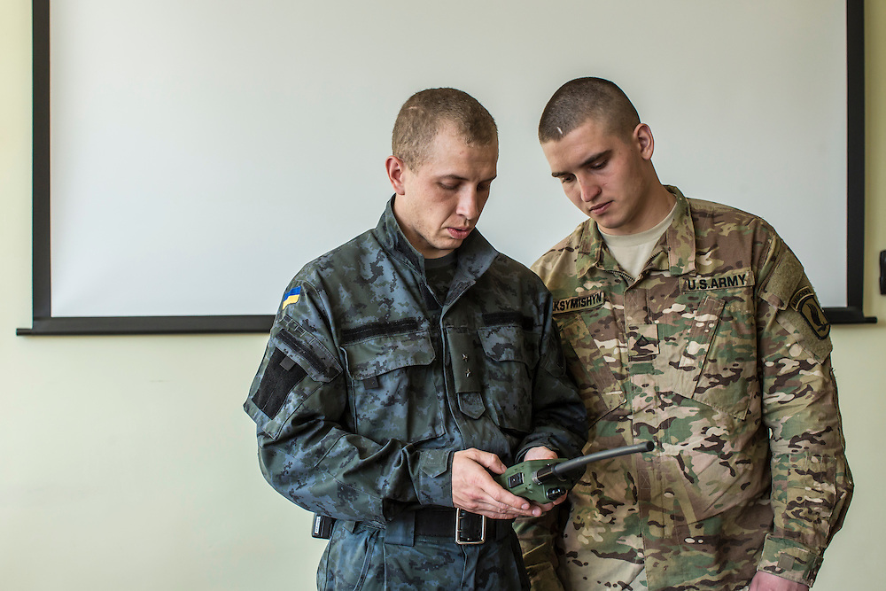 YAVORIV, UKRAINE - APRIL 30, 2015: A Ukrainian soldier and a member of the U.S. Army's 173rd Airborne Brigade review the use of a communication radio provided by the United States to the Ukrainian army, a component of military training under Operation Fearless Guardian at the Yavoriv training center near Yavoriv, Ukraine. Around 300 American soldiers are training an equivalent number of Ukrainians during each of three eight-week programs to improve their ability to combat Russian-backed rebels in the country's east. CREDIT: Brendan Hoffman for The New York Times