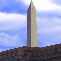 The Washington Monument rises above a nearby Washington, DC building. Undated.