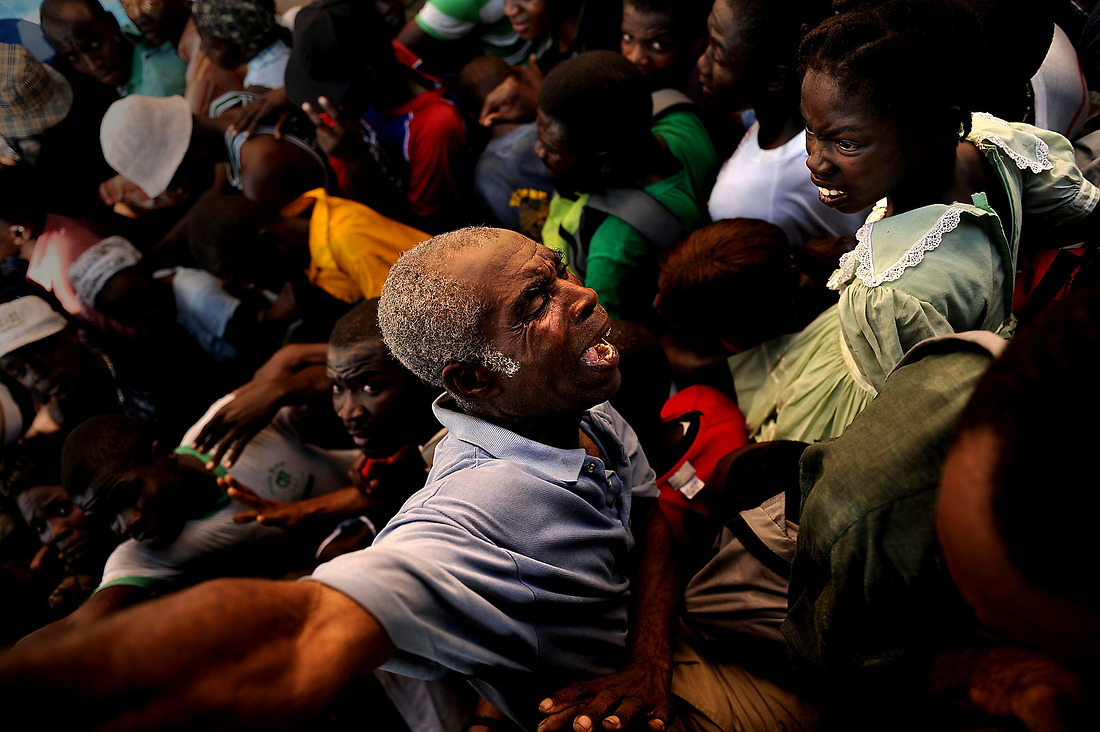 An older man is crushed while he tries to get out of the way of a huge number of Haitians making their way to the relief supplies (food and water) the U.S. Army Soldiers with the 82nd Airborne Division, Fort Bragg, North Carolina, were handing out on January 20, 2010, at the stadium in Port au Prince, Haiti, for Operation Unified Response. As more and more Haitians heard of the distribution being handed out by the soldiers, the distribution line turned into a huge gathering of people being pushed from the back. The soldiers stood their ground and handed out the majority of the relief for as long as they could, before they were hugely outnumbered and overrun. A devastating earthquake hit the region on January 12, 2010. Since then USSOUTHCOM has distributed more than 636,951 bottles of water and more than 473,325 Humanitarian Daily Rations. — © Master Sgt. Jeremy Lock/