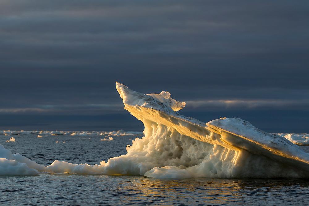Canada, Manitoba, Churchill, Melting iceberg on Hudson Bay at sunset on sunny summer evening