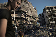 Gaza Strip, Beit Lahia: Palestinian men are seen in front of destroyed buildings in Beit Lahia, located less than two kilometres from the northern crossing point between Israel and the Gaza Strip on August 2, 2014. ALESSIO ROMENZI
