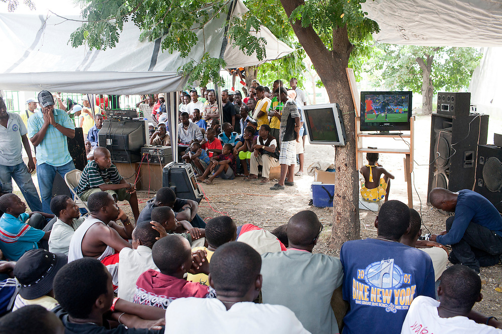 People crowd around several television sets to watch the World Cup final on July 11, 2010 in Port-au-Prince, Haiti.
