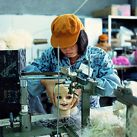 Migrant worker sewing blond hair onto a doll in a Joint Venture toy factory, producing both for export and the Chinese market...From China [sur]real © Mark Henley..