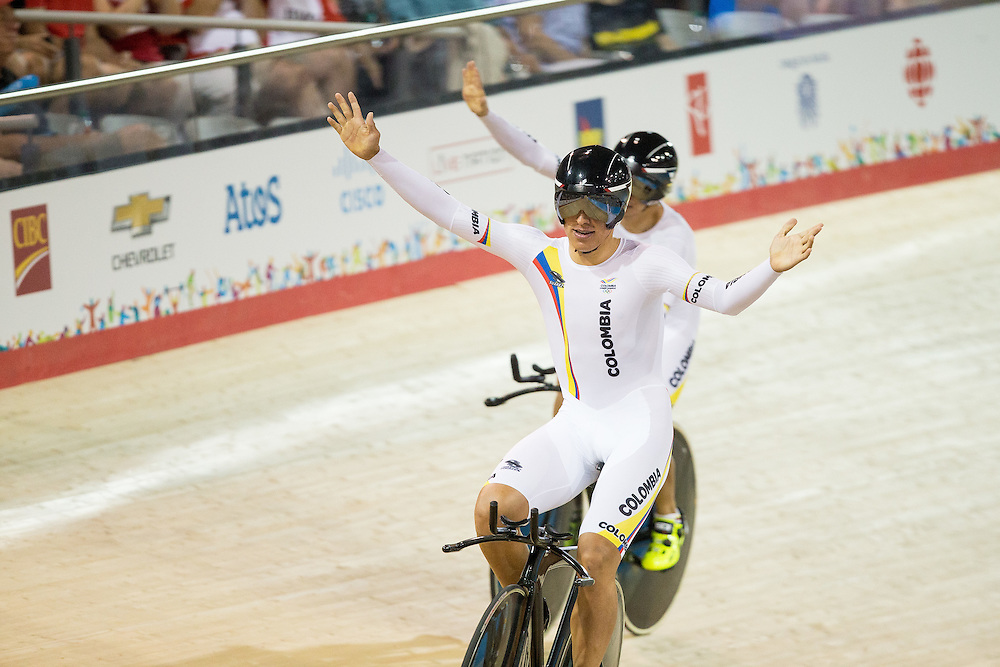 Juan Esteban Castro Laverde (L) of Colombia and teammate Santiago  Restrepo Valencia celebrate their gold medal win in the men's cycling team pursuit at the 2015 Pan American Games in Toronto, Canada, July 19,  2015.  AFP PHOTO/GEOFF ROBINS