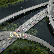 "Unknown to motorists below, a message of love to an unknown ""Gina"" is scrawled across the lanes of an overpass on Highway 520 in the Arboretum on Tuesday, June 12, 2007 in Seattle.  The message was painted on an unused ramp on the highway in the serene park.   The painter and the recipient of the message are mysteries.  Photo by Joshua Trujillo / Seattle Post-Intelligencer"