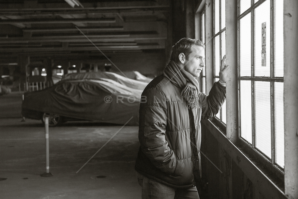 man in a winter coat standing by a window in a parking garage