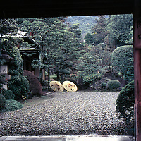 Two pale yellow parasols seen through Kyoto courtyard gate