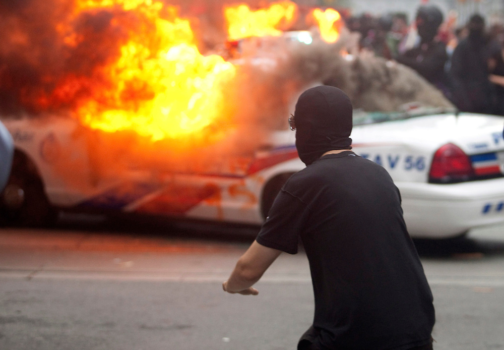 Protesters smash police vehicles in the Toronto's downtown core June 26, 2010 after a small group of anarchists broke from the main anti G20 demonstration and began a destructive march through the downtown..AFP/GEOFF ROBINS/STR