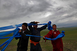 Mongolian worshippers tie blue colored scarves, symbolic of the 'open sky' or 'Tengri',  to poles surrounding the as the 'Ovoo' or 'sacred stone' site for Mongolian Shaman brothers Gankhuyag and Batgerel Batmunkh during a  Shaman ceremony by  on Black Mountain Head in Nalaikh district of Ulan Bator in Mongolia, 06 July 2012. The Shaman ceremony is held for a family to give offerings to the spirits of nature and to bring good karma to the members of family.  The scarves of color blue is symbolic of the 'open sky' or 'Tengri' while red represents 'fire'; orange for 'sand' and white for 'milk'. Shamanism comes from the term 'shamans' that refers to priests or mediums that acts as vessels for spirits, gods and demons to communicate with the human world. In Mongolia, they adhere to the ancient beliefs of Tengrism, where spirits live in all of nature, in the sun, moon, lakes, rivers, mountains, and trees.