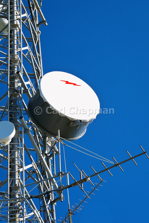 Microwave dish antenna on communications tower for the cellular telephone system.