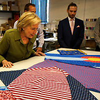 U.S. Democratic presidential nominee Hillary Clinton looks at scarves at Knotty Tie, a local tie company in Denver August 3, 2016. REUTERS/Rick Wilking