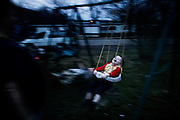 Michelle Goins pushes her son Jonathon on the swing at dusk as the sun fades over Chauncey, Ohio on March 9, 2006.