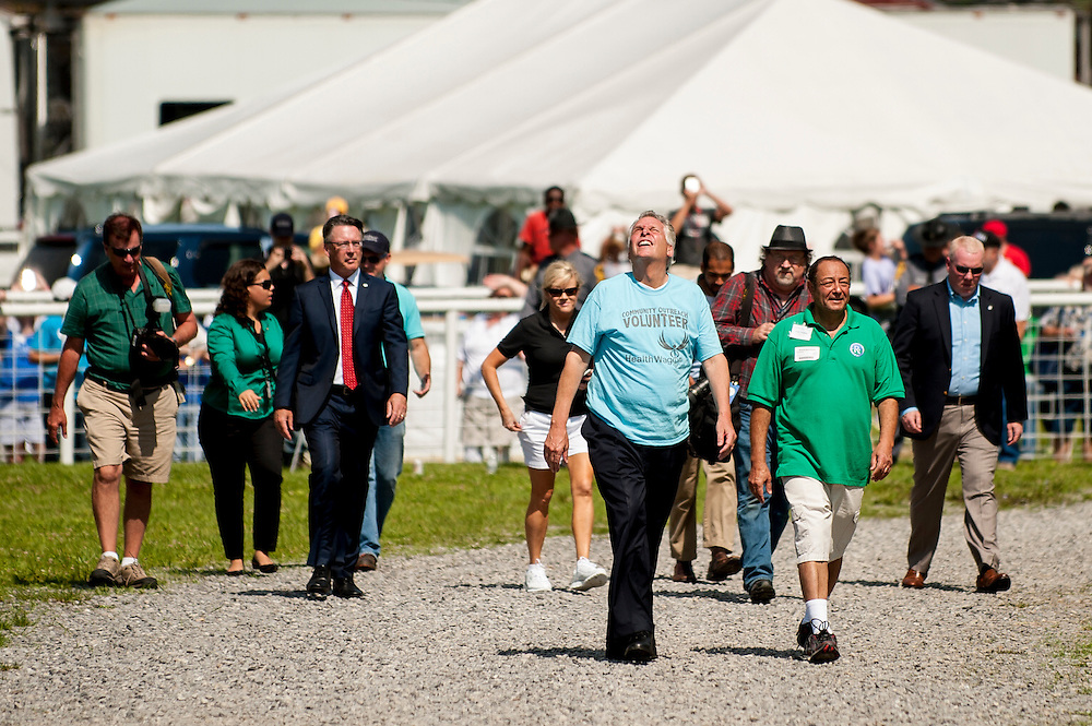 Virginia Governor Terry McAuliffe (center) looks up at an unmanned, six-rotor aircraft that had just delivered supplies and medicine to thousands of people seeking dental and medical care at the Remote Area Medical clinic at the Wise County Fairgrounds in Wise, Virginia, U.S., on Friday, July 17, 2015. The flight, called &ldquo;Lets Fly Wisely,&rdquo; was done in part to study how the technology could be used in future humanitarian crises around the world, made history as the first FAA approved package delivery in the United States.<br /> RAM is a nonprofit that delivers free medical care to people living in rural areas. Photographer: Pete Marovich/Bloomberg