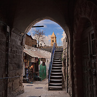 Habad Street, a narrow, partially covered street in the Jewish Quarter of the Old City of Jerusalem. The Lutheran Church of the Redeemer is visible in the background.