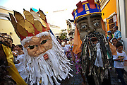 Costumed revelers parade through the streets of Old San Juan during the Festival of San Sebastian in San Juan, Puerto Rico.