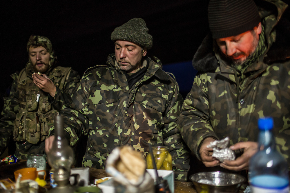 PERVOMAISKE, UKRAINE - NOVEMBER 19, 2014: Members of the Dnipro-1 brigade, a pro-Ukraine militia, eat dinner at their base under a bridge in Pervomaiske, Ukraine. CREDIT: Brendan Hoffman for The New York Times