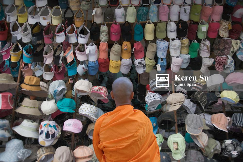 Monk at hat shop.