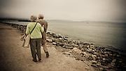 An elderly couple walk down a path near Crissy Field, San Francisco, California, USA.