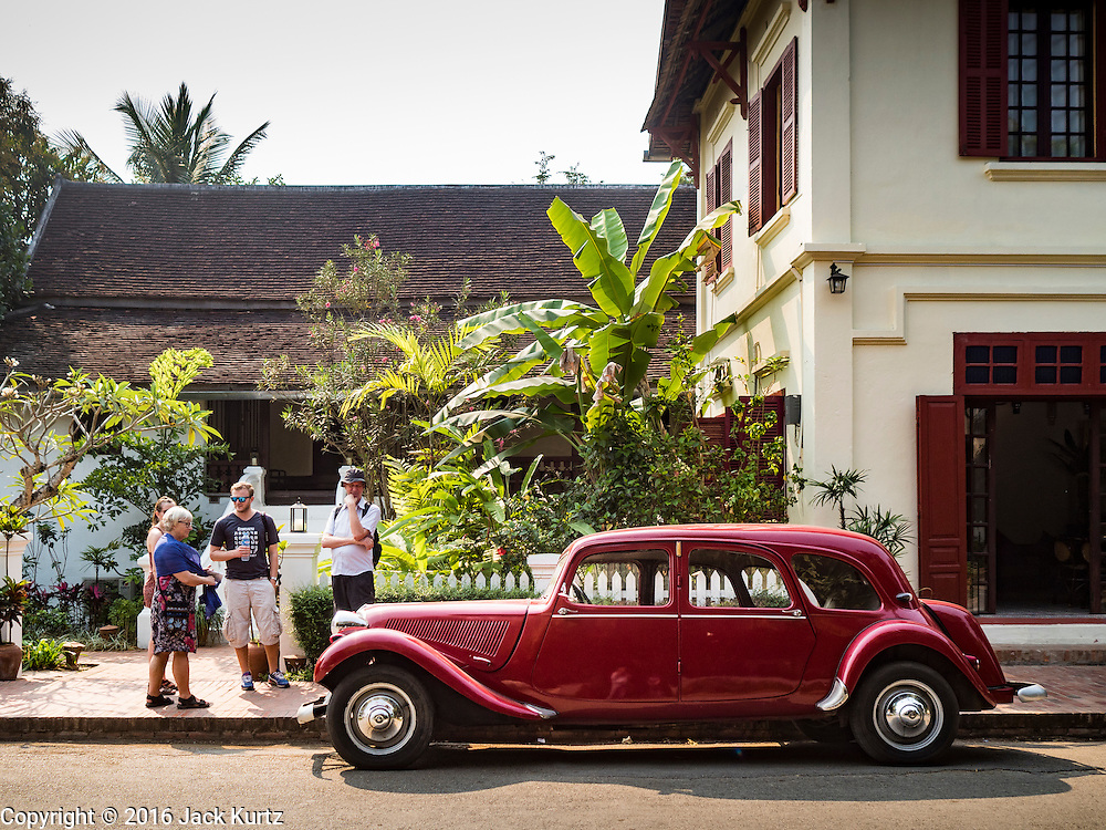 """13 MARCH 2016 - LUANG PRABANG, LAOS:  Tourists look at a 1952 Citroen Model 11, one of only two of that model in Laos, at 3 Nagas, one of the most upscale hotels in Luang Prabang. Luang Prabang was named a UNESCO World Heritage Site in 1995. The move saved the city's colonial architecture but the explosion of mass tourism has taken a toll on the city's soul. According to one recent study, a small plot of land that sold for $8,000 three years ago now goes for $120,000. Many longtime residents are selling their homes and moving to small developments around the city. The old homes are then converted to guesthouses, restaurants and spas. The city is famous for the morning """"tak bat,"""" or monks' morning alms rounds. Every morning hundreds of Buddhist monks come out before dawn and walk in a silent procession through the city accepting alms from residents. Now, most of the people presenting alms to the monks are tourists, since so many Lao people have moved outside of the city center. About 50,000 people are thought to live in the Luang Prabang area, the city received more than 530,000 tourists in 2014.   PHOTO BY JACK KURTZ"""