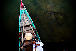 Bird's eye view of a man sleeping in his barge, Hoi An, Vietnam, Southeast Asia