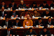 A monk sits among fellow delegates at a plenary session of the Chinese People's Political Consultative Conference, at Beijing's Great Hall of the people Beijing, China, Saturday, March 7, 2009. China's National People's Congress is a largely powerless body but it represents one of the country's last displays of old style communism. Ethnic minority delegates from around the country attend the meetings wearing traditional costumes, a conceit which allows the government to argue that the nation's different cultures co-exist harmoniously. Little is decided at these gatherings though. The NPC functions largely as a rubber stamp body for policies put forward by the Communist party's elite.