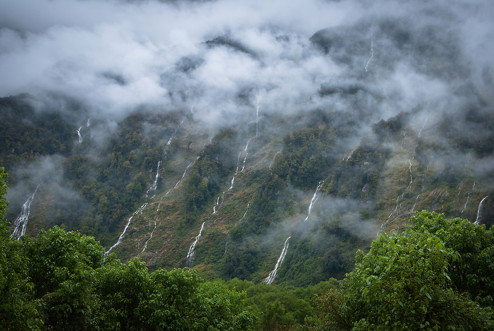 Multiple waterfalls decscend the steep, cloud-covered sides of the Arthur Valley; Milford Track, New Zealand