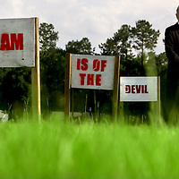 "GAINESVILLE, FL -- August 18, 2010 -- Pastor Terry Jones poses for a portrait with signs along the road that state ""Islam is of the Devil"" at the Dove World Outreach Center in Gainesville, Fla., on Wednesday, August 18, 2010.  The signs have been replaced multiple times after vandalism.  The church is planning on burning multiple copies of the Koran on the anniversary of the September 11th terrorist attacks.  (Chip Litherland for The New York Times)"