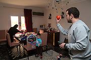 CAIRO, EGYPT - FEBRUARY 25: Al Jazeera English (AJE) producer Baher Mohamed (r) plays basketball with his son Hazem as wife Jehan Rashed helps daughter Fairouz at the family table February 25, 2015 at their family apartment in the Sheikh Zayed district on the outskirts of Cairo, Egypt. Baher, and fellow Al Jazeera defendent Mohamed Fahmy were conditionally released on Feb 12, 2015 following Egypt's highest appeal courts decision to grant them a retrial, which has since been postponed until March 8. (Photo by Scott Nelson, for the Washington Post)
