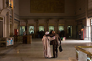 Friends greet each other warmly in the booking hall of the main railway station in Luxor, Nile Valley, Egypt.