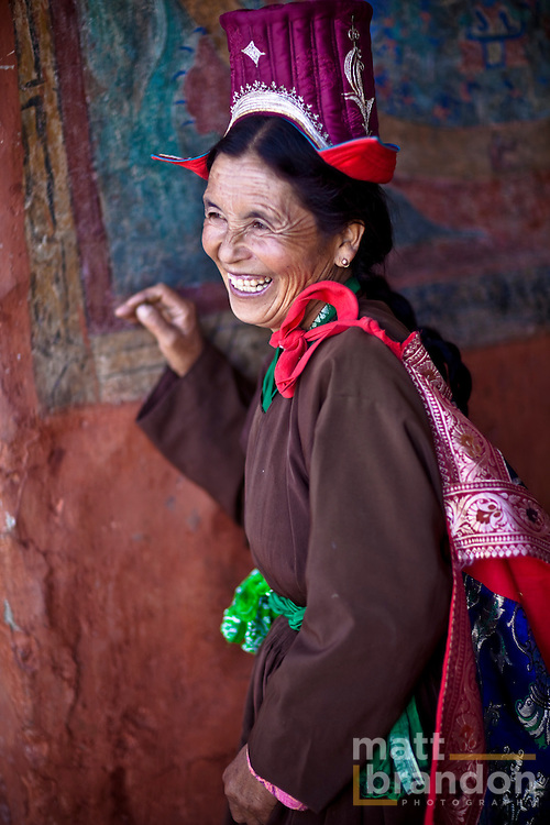 A Ladakhi woman laughs as she stands in traditional  clothing in a Buddhist monastery.