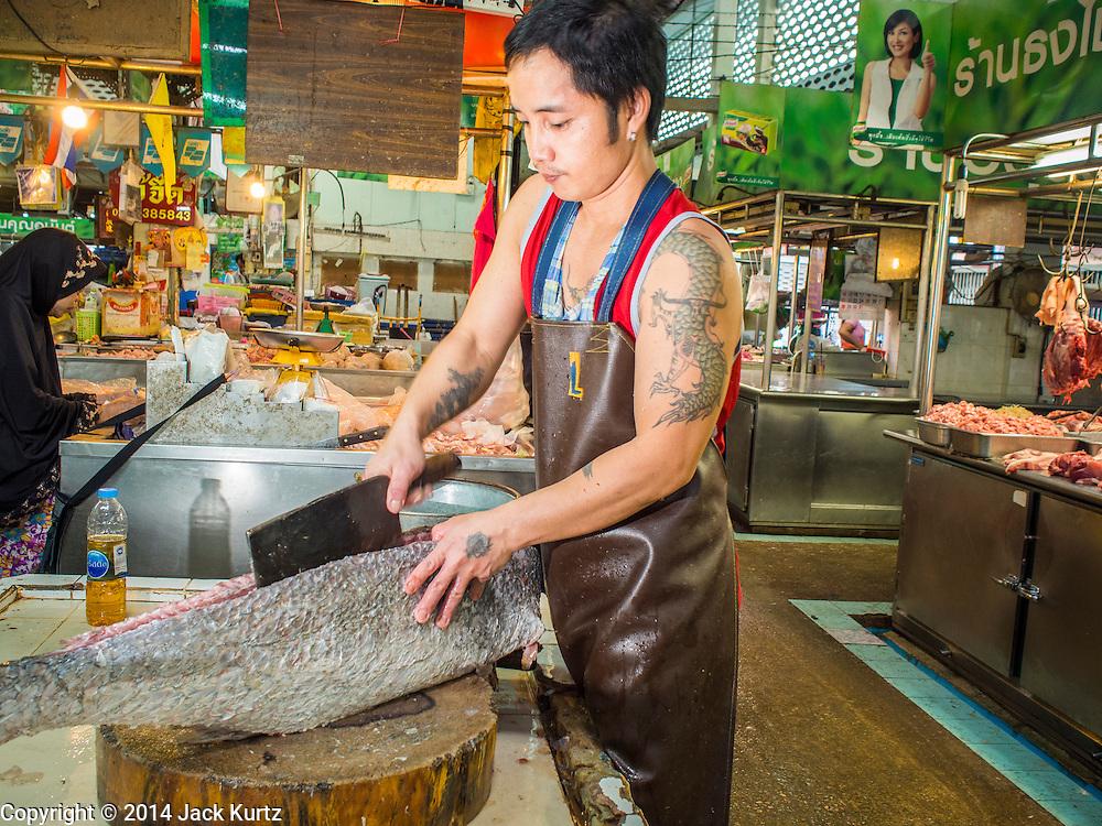 09 DECEMBER 2014 - THONBURI, BANGKOK, THAILAND: A fish seller cuts up a fish in his market stall in the Thonburi section of Bangkok.    PHOTO BY JACK KURTZ
