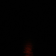 Bright Orange Moonrise over the Atlantic Ocean at Jekyll Island with reflection in the sea.