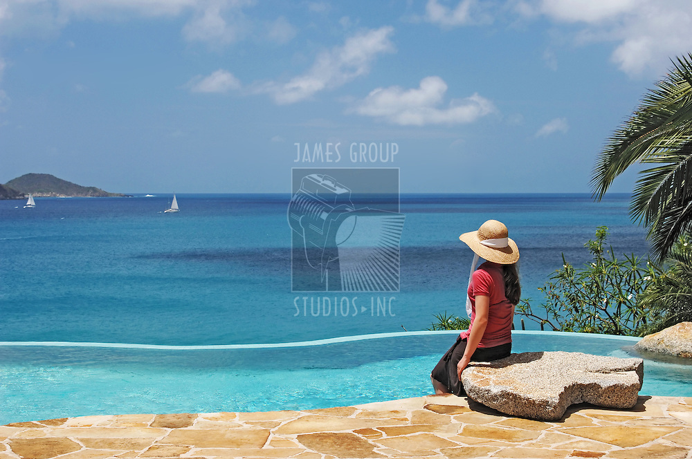 A young girl siting by pool at a tropical resort looking out to the ocean