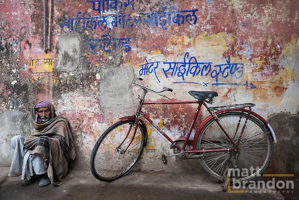 """An Indian man sits against the wall by his bike. The writing on the wall read """"bicycle parking here""""."""