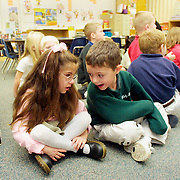 """ANNABELLE -- des moines, dec. 17 -- Annabelle Costanzo visited with her kindergarten classmate Max Guest while other students engaged in an activity.  Earlier that day during their morning prayers another classmate, Adam Chelleen, prayed that Annabelle would """"get unblind"""".    .   The children """"love her so much,"""" says Gina Costanzo, Annabelle's mother.  """"They're so good for her."""" photo by david peterson"""