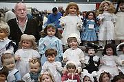 Een handelaar biedt op de Verzamelaarsjaarbeurs in de Jaarbeurs in Utrecht poppen aan.<br /> <br /> A trader is showing his dolls at the collectors fair.
