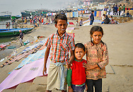 Boy with this brother and sister, brushing teeth, dawn on the Ganges, Varanassi, India