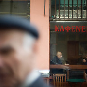 Walking past one of Athens' classic Kafenions (cafe's) in the area of Thissio. Thissio is a place famous for its great number of cafés and bars, with a beautiful view on the Acropolis. Some of the first ever cafes in Athens where situated in this area. Image © Angelos Giotopoulos/Falcon Photo Agency