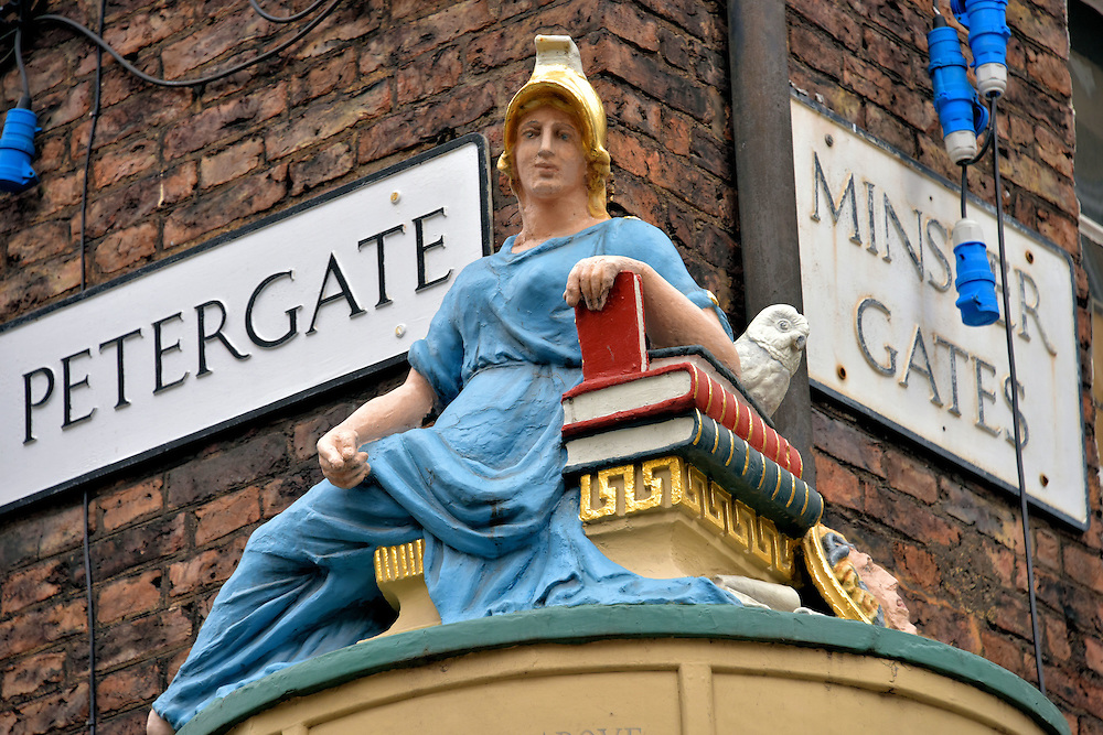 Minerva Statue in York, England<br /> Minerva was the daughter of Jupiter and the Roman goddess of drama and the arts. This 1801 sculpture by John Wolstenholme portrays her with a white owl, a symbol of her wisdom. Her left arm rests on books. This is a tribute to John Foster&rsquo;s former store. The bookseller occupied this intersection of Petergate and Minster Gates from 1580 until 1607. The street is better known as Stonegate.  Beneath it is an ancient road called Roman Via Praetoria.