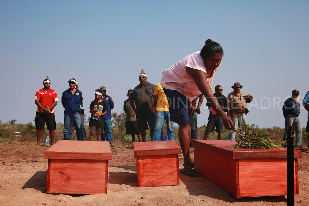 A woman cleansing the wooden coffins with a white gum tree leaf which is also used in ceremonies. . In the Bidyadanga community the remains of 17 Kimberley Aboriginal people have been returned home more than a century after they were taken and put on display in museums around Australia. And are now buried on a hill near the beach. The repatriation of skeletal remains collected by scientists and now returned to their ancestral homes. Bidyadanga community , WA